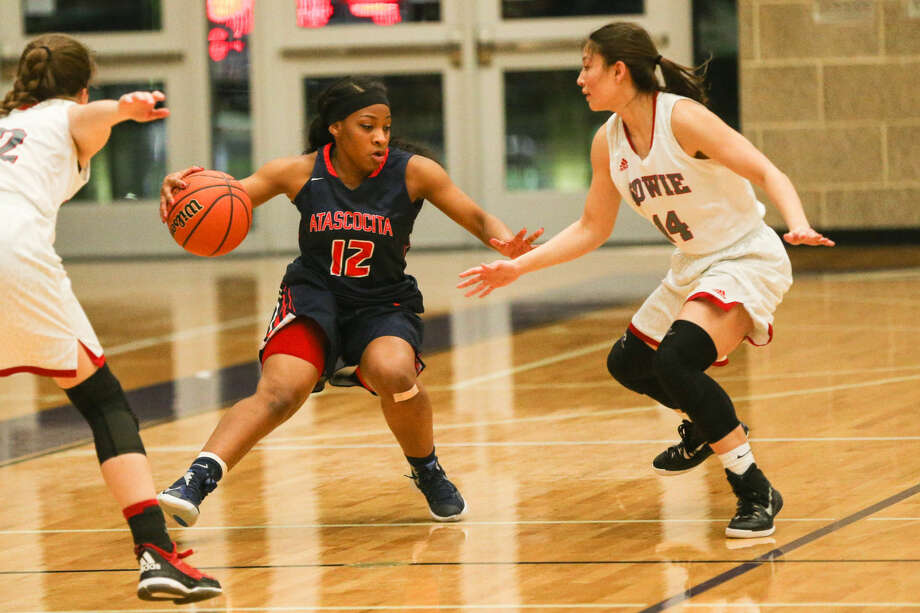 Atascocita guard Aimee Brown tries to get past Austin Bowie defenders during the high school girls basketball game on Friday, Feb. 19, 2016, at College Station High School. To view more photos from the game, go to HCNPics.com. Photo: Michael Minasi