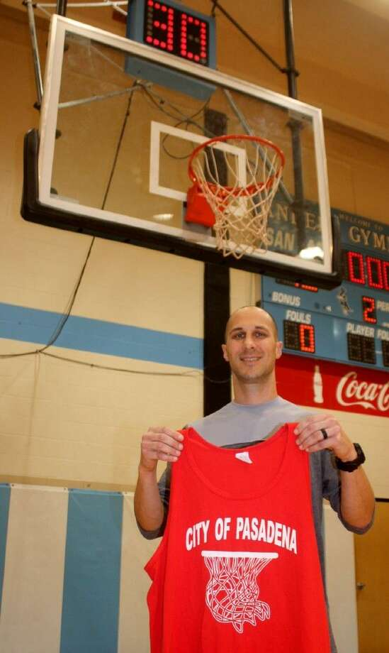 Holding a youth basketball jersey from Pasadena's Parks & Rec league, San Jacinto College head coach Scott Gernander is inviting all youngsters who play in a youth league to come out to Saturday's 4 p.m. game and cheer on the Ravens as they play Lamar State-Port Arthur at Anders Gym. Miniature basketballs will be handed out to every youngster. Photo: Robert Avery