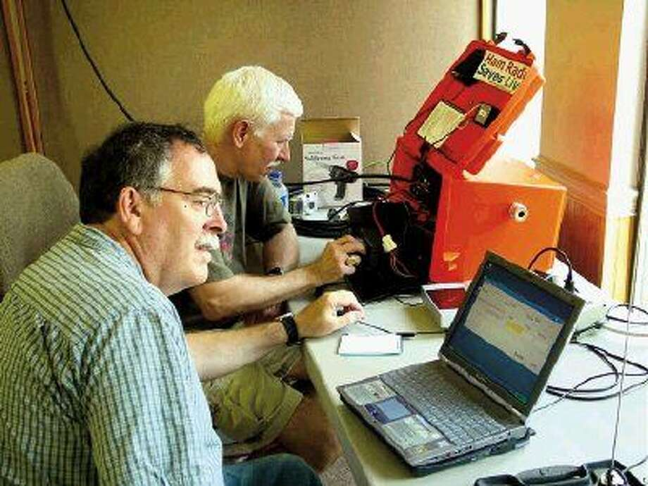 Pictured at a recent Field Day are Bruce Bayley, KC5ABR, logging contacts on the computer (front) and John Psimas, KE5MSE, at the radio (back).