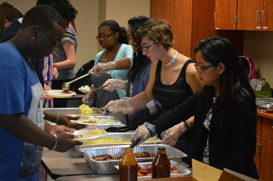 Clear Springs High School Students and members of the French honor Society serve Texas BBQ to students visiting from France.