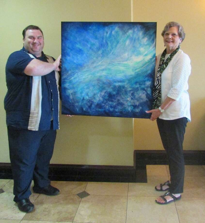 """Pictured, left to right, are Sheldon Green, General Manager of Holiday Inn Express and Suites and artist Margo I. Green with her painting """"Heaven's Hand."""""""