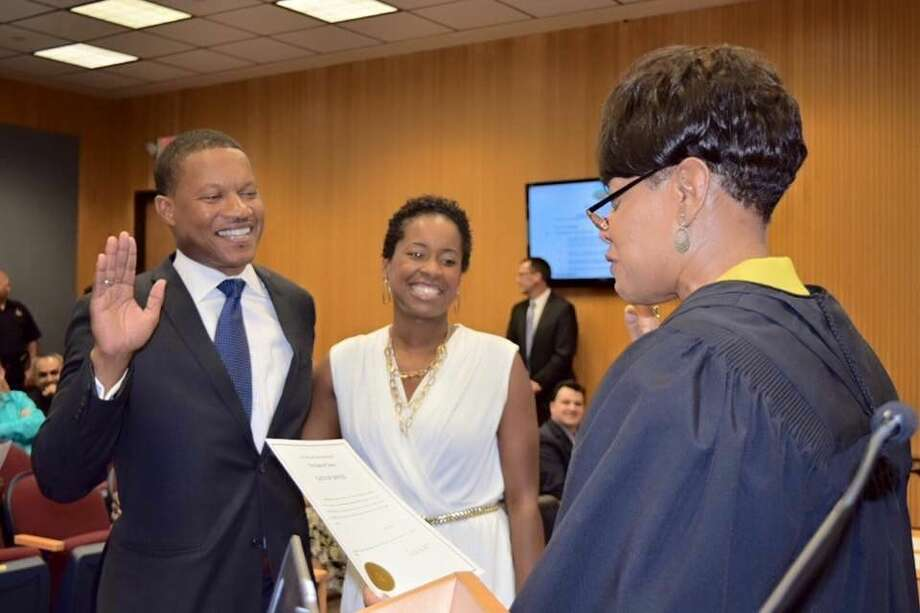 Derrick Reed, with wife Erin, is sworn in by the Honorable Belinda Hill.
