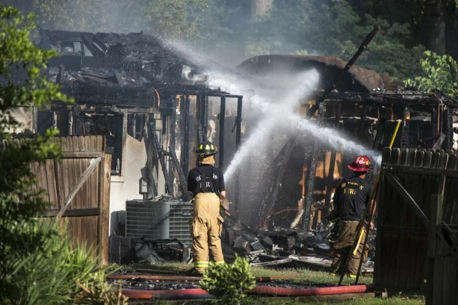 Firefighters water down the scene of a two-alarm house fire in the 1400 block of Mistletoe Lane on July 9, 2014, in Kingwood. Photo: Andrew Buckley