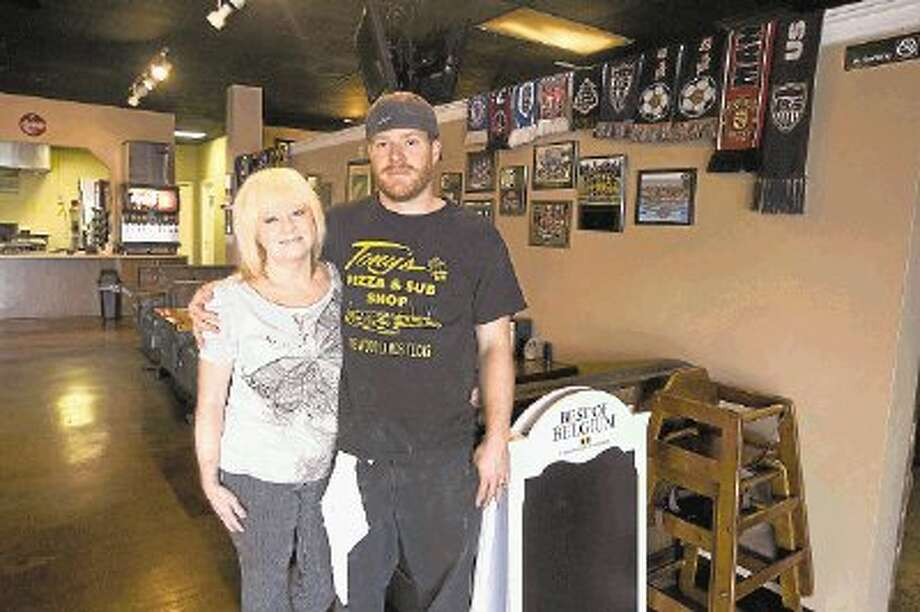 Ryan D'Avignon poses for a photo with his mom, Barbara, who helps her son with Greek Tony's Pizza in Spring. The family oriented restaurant was opened by Ryan's dad, Greg D'Avignon, who passed away in 2011. The establishment remains a go-to spot for local sports teams and sports fans. Photo: Jason Fochtman / Conroe Courier / HCN