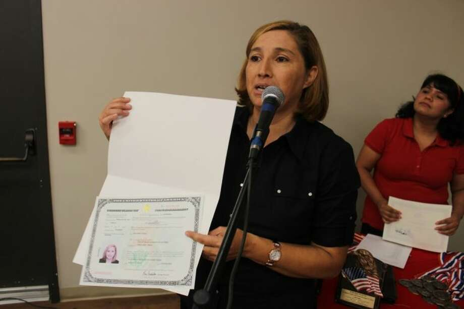 Legal immigrant Liliana Aguirre, originally from Mexico, shows off her certificate as Maria de Lourdes Navarro, also a citizen, looks on Friday at the Conroe Activity Center.