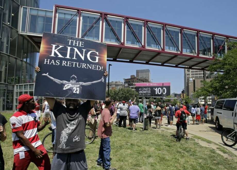 Graphic designer Alvin Smith holds up a poster across the street from the Quicken Loans Arena on Friday in Cleveland, heralding the return of LeBron James.