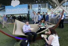 Simon Driscoll and Nicola Band, from Scotland, settle into a hammock for lunch with colleague Freya Crawshaw at the Dreamforce conference hosted by Salesforce at the Moscone Convention Center in San Francisco, Calif. on Tuesday, Oct. 4, 2016.