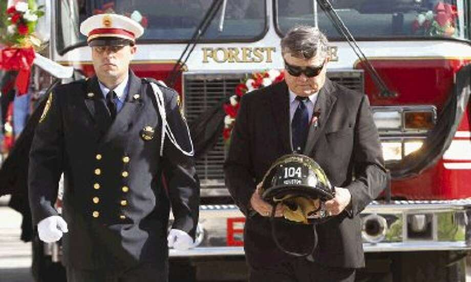 The helmet of fallen firefighter Daniel Groover is taken toward The Woodlands Church campus for a public memorial service Saturday. The 21-year veteran of the Houston Fire Department was killed while battling a house fire in the Forest Cove subdivision of Kingwood Wednesday. Go to HCNpics.com to view more photos from the public memorial service. Photo: Jason Fochtman / Conroe Courier