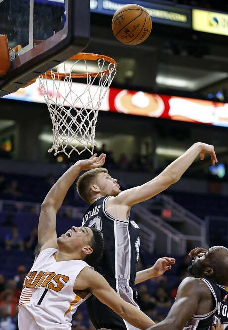 San Antonio Spurs' Davis Bertans, middle, blocks the shot of Phoenix Suns' Devin Booker (1) as Spurs' Joel Anthony, right, watches during the second half of an NBA preseason basketball game Monday, Oct. 3, 2016, in Phoenix. The Suns won 91-86. (AP Photo/Ross D. Franklin) Photo: Ross D. Franklin/Associated Press