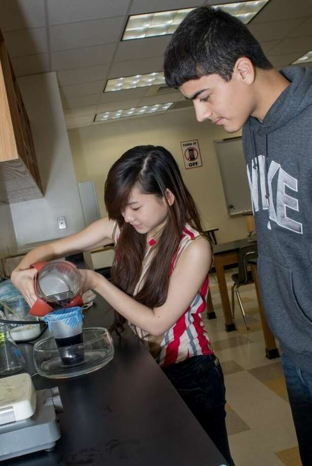Upward Bound students Vy Nguyen (left) and Christopher Martinez participate in a science experiment during a six-week academic summer camp taking place at Lone Star College-North Harris. Photo: Submitted Photo