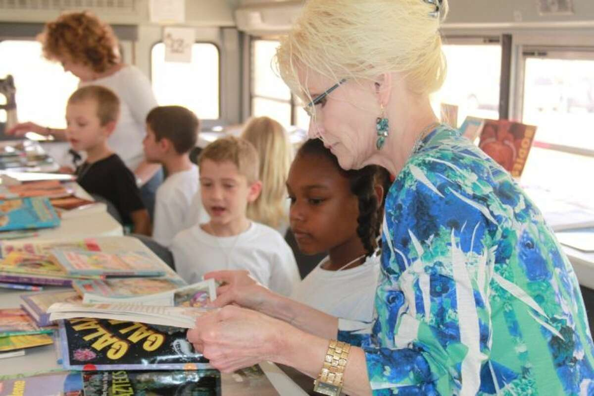 Dawn Berger helps camper Tatum Williams in selecting a book from the Liberty ISD Bookmobile during Camp Invention.