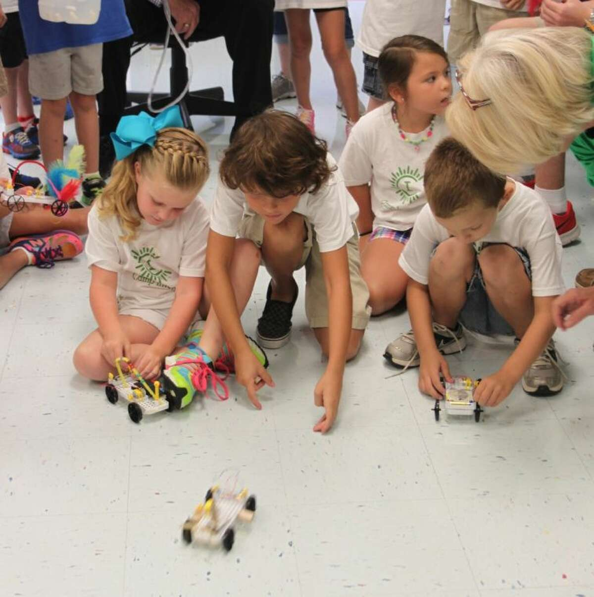 Emily Hebert, Parker Balch, Summer Balch and Trey Lott race the battery-powered cars they created at Camp Invention, held at San Jacinto Elementary in Liberty during the week of July 7-11. They are being assisted by Jo Ann Gilliland.