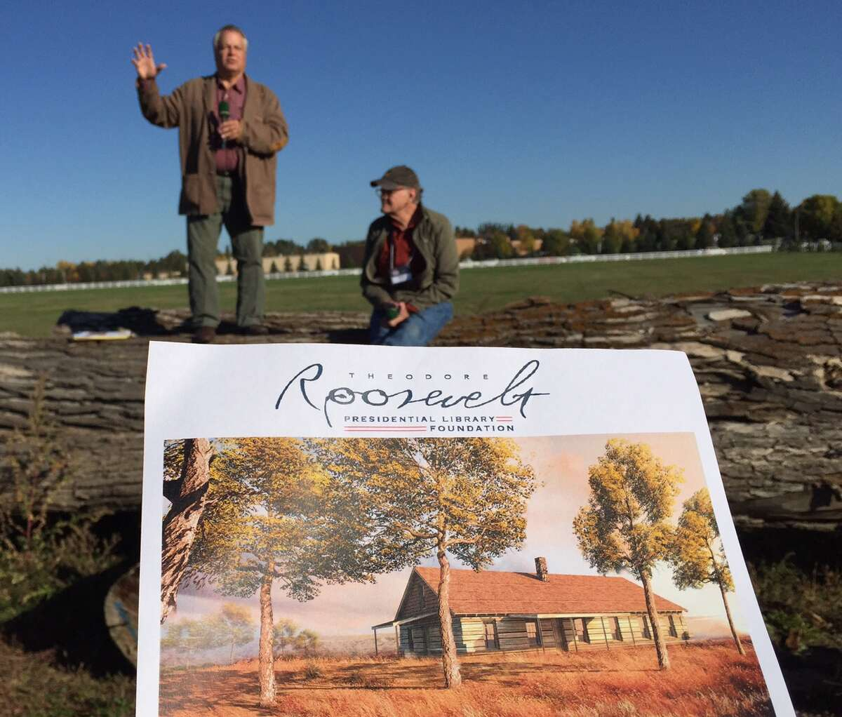 An artist's rendering of a planned reproduction of Theodore Roosevelt's 1885 Elkhorn Ranch cabin is in the foreground with Clay Jenkinson, left, and Dr. Bruce Pitts, board chair of the heodore Roosevelt Presidential Library & Museum at Dickinson State University in Dickinson, ND (Paul Grondahl / Times Union)