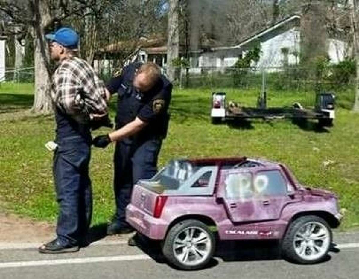 Deputy Nathan Deweese (right) arrests David Schumaker (left) for allegedly committing credit card abuse. Schumaker, seen in this photo from Facebook, reportedly was seen driving around in the small, pink Cadillac Escalade Power Wheels toy car pictured here. The San Jacinto County Sheriff's Office received calls about him driving the car around Shepherd.