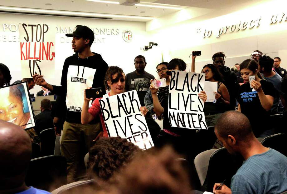Black Lives Matter protesters demonstrate inside the board of Police Commissioners meeting in Los Angeles on Tuesday, Oct. 4, 2016. Los Angeles police released surveillance video Tuesday showing an 18-year-old black suspect running from police while holding what appears to be a gun in his left hand just before he was fatally shot by officers in a death that has generated rowdy protests. (AP Photo/Nick Ut) Photo: Nick Ut, STF / Copyright 2016 The Associated Press. All rights reserved.