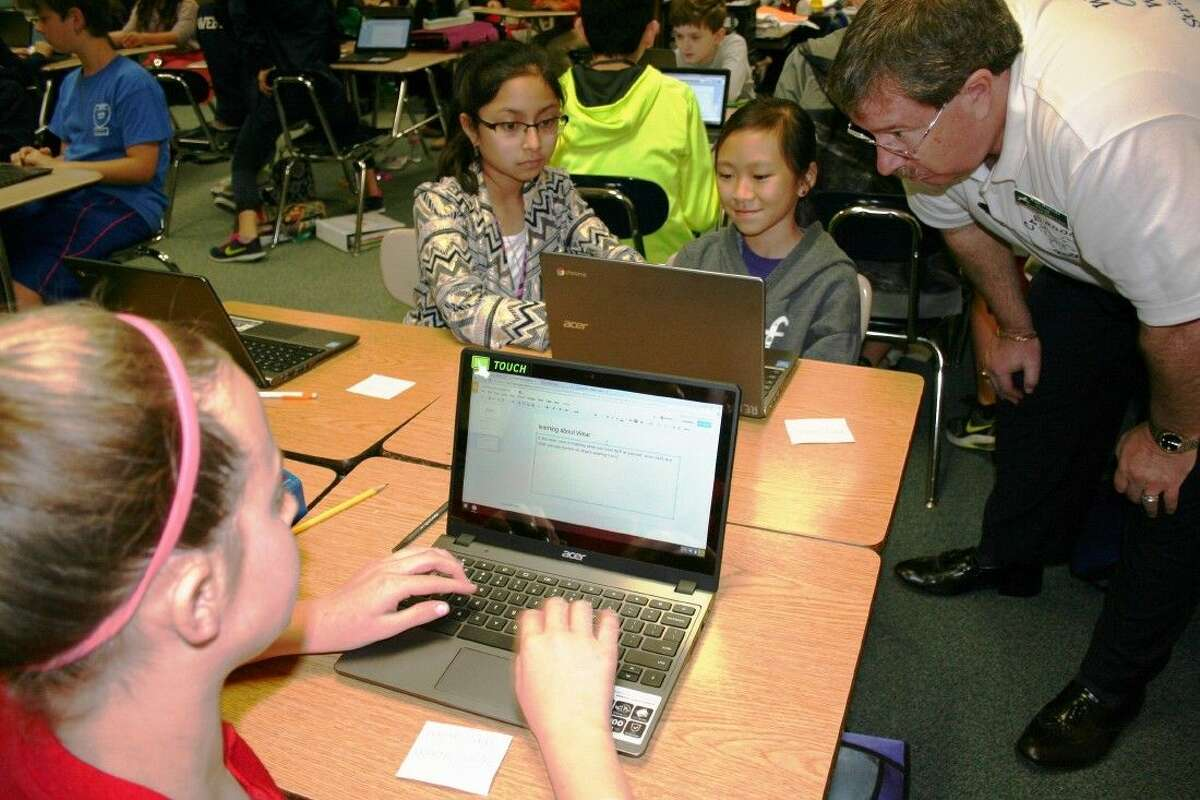 Creekwood Middle School sixth graders Stephanie Hinh, Cindy Cupples, and Kathryn Pratt demonstrate to Principal Walt Winicki how they are using the new Chromebooks to complete an assignment in Google Classroom.