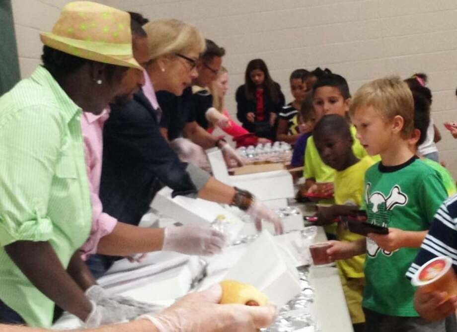 Community volunteers serve a breakfast provided by Kingwood Medical Center to children attending the Lake Houston YMCA's summer day camp.