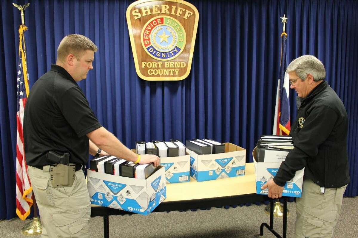 Fort Bend County Sheriff's Office Sgt. Rodney Grimmer, left, and Lt. David Schultz, right, are shown with just a portion of the records reviewed in Lamar CISD case.