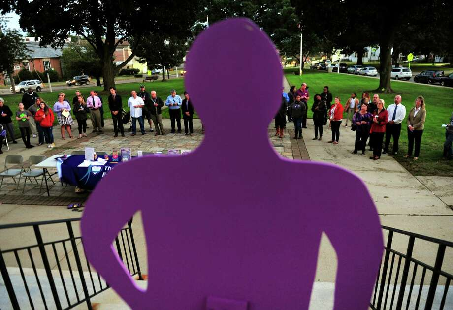 A cut-out of a person, which represents a silent witness, looks out over attendees during a Domestic Violence Awareness Vigil held by The Center for Family Justice at the Stratford Town Hall Green in Stratford, Conn. on Tuesday Oct. 4, 2016. The vigil coincides with a law that has just been enacted to take away firearms from anyone in the process of having a court order protection from abuse being filed against them. Photo: Christian Abraham / Hearst Connecticut Media / Connecticut Post