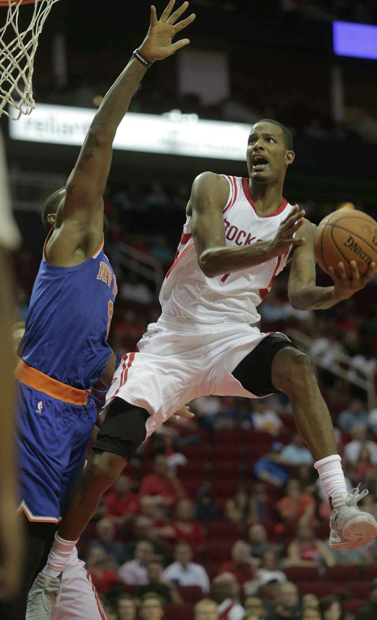 Houston Rockets forward Trevor Ariza (1) is fouled by New York Knicks forward Kyle O'Quinn (9) in the first half of game action at the Toyota Center on Tuesday, Oct. 4, 2016, in Houston.