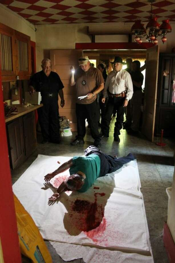 A faked murder-suicide scene was set up in a Daisetta house on July 24 as part of a training event for the Liberty County Sheriff's Office. In this photo, Deputy William Candelari (holding flashlight) gathers evidence with the assistance of Pct. 2 Justice of the Peace Ronnie Davis (left) and Daisetta Police Chief Mike Parrish. Photo: VANESA BRASHIER