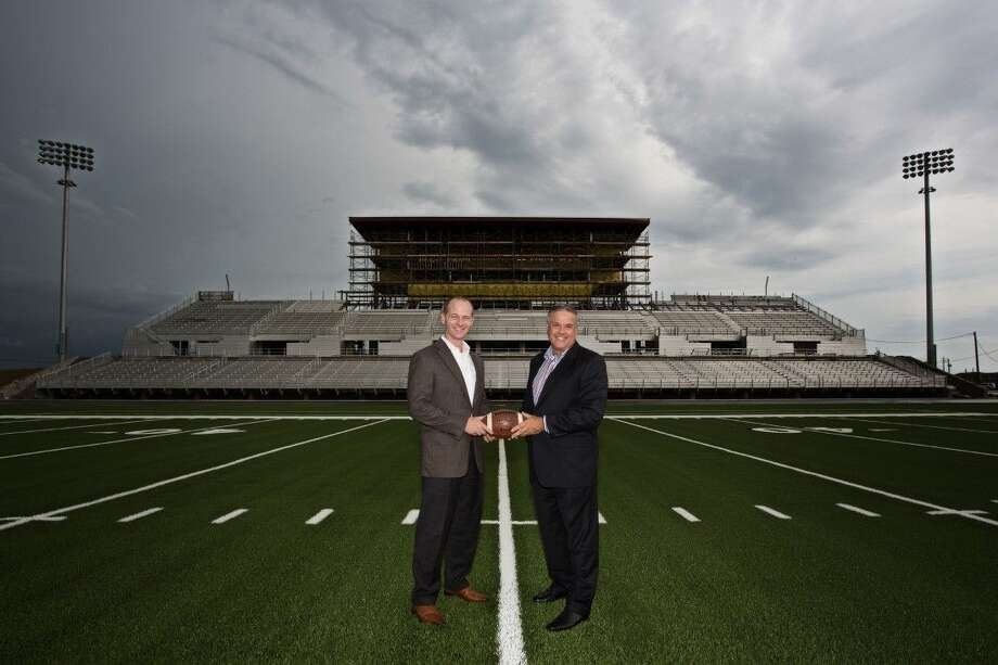 CCISD Superintendent Dr. Greg Smith (right) welcomes Houston Methodist St. John Hospital CEO Dan Newman to the team at the 50-yard line of CCISD Challenger Columbia Stadium. Photo: SUBMITTED PHOTO