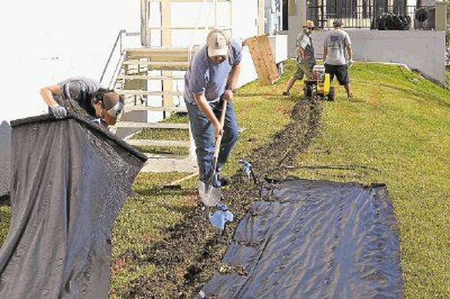 The Physicians at Sugar Creek team puts down irrigation lines in preparation for planting boxes at the clinic's community garden