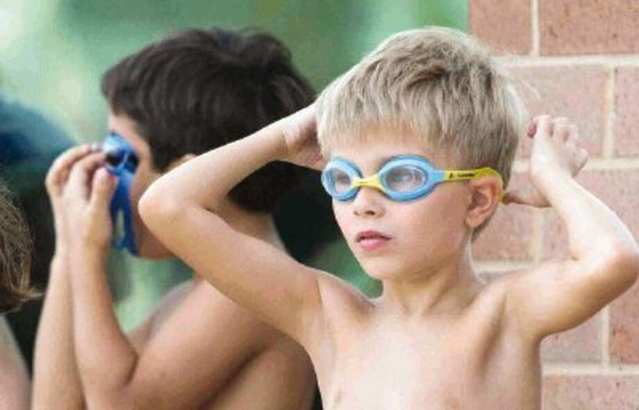 Connor Henry puts on his goggles before the start of the YMCA Youth Triathlon Kiwanis Kids Series at Branch Crossing YMCA Saturday. More than 170 kids ages 7-12 competed in the triathlon. To view or purchase this photo and others like it, visit HCNpics.com. Photo: Jason Fochtman / Conroe Courier / HCN