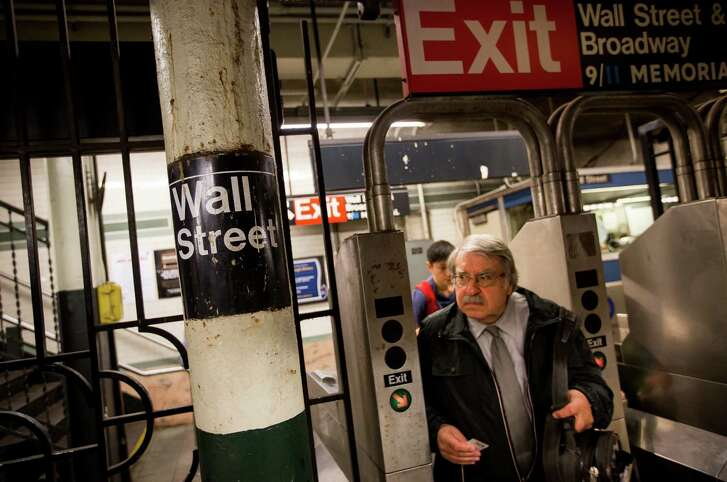 A man  passes through a turnstile at the Wall Street subway station. Reports show many investors  are selling stocks and buying bonds.