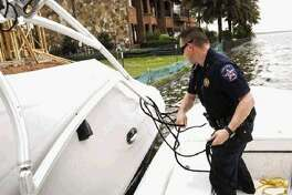 Montgomery County Precinct 1 Constable's Lt. Tim Cade secures a boat that was found drifting on Lake Conroe after water levels surged 2 feet above the maximum capacity Friday.