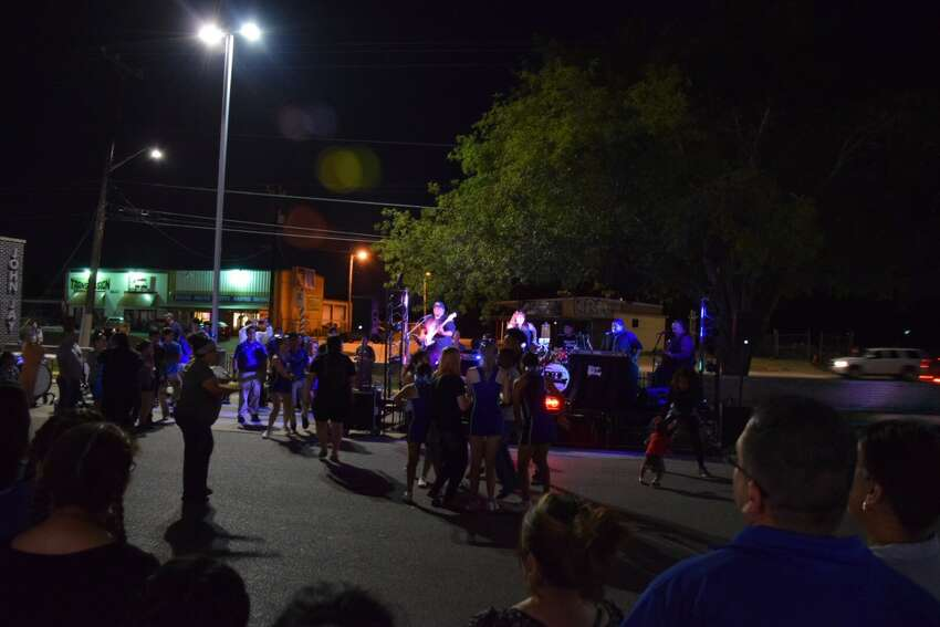 Cheerleaders and other attendees dance to the band MixTape at John Jay High School's National Night Out on Tuesday.
