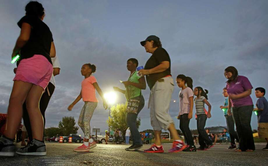 Neighbors line-dance  during the Jupe Manor Neighborhood Association annual National Night Out event. A visitor comments on the value of such citizen unity. Photo: Ron Cortes /For The San Antonio Express-News