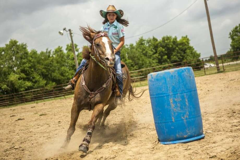 Barrel racer Tara Jo Segovia, 10, takes a corner during a practice session July 31, 2014, at the Dayton Huffman Horse Center in Dayton. Photo: Andrew Buckley