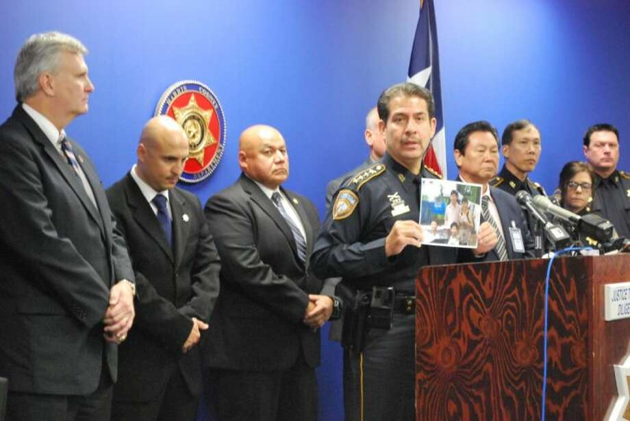 Harris County Sheriff Adrian Garcia holds up a picture of the Sun family at a press conference on Wednesday. The Cypress family was found murdered in their home in January. HCSO investigators are looking for clues to solve the six-month old murder. Photo: Submitted