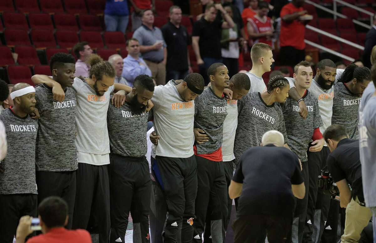 Following in the path of other NBA teams, members of the Rockets and New York Knicks make a show of unity during the playing of the national anthem before their preseason game Tuesday night at Toyota Center. The Rockets won 130-103.