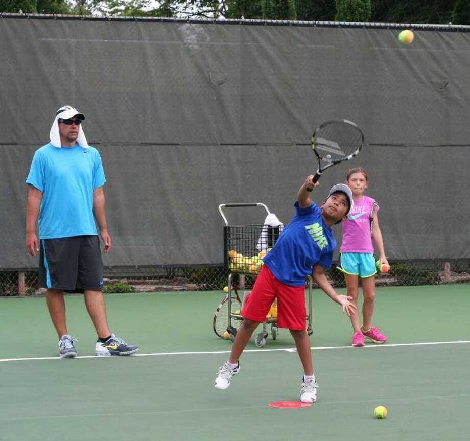 Ten-and-under Director Matt Snyder and Andie Thomas look on as Praneeth Kongora serves the ball during a recent lesson at Giammalva Racquet Club.