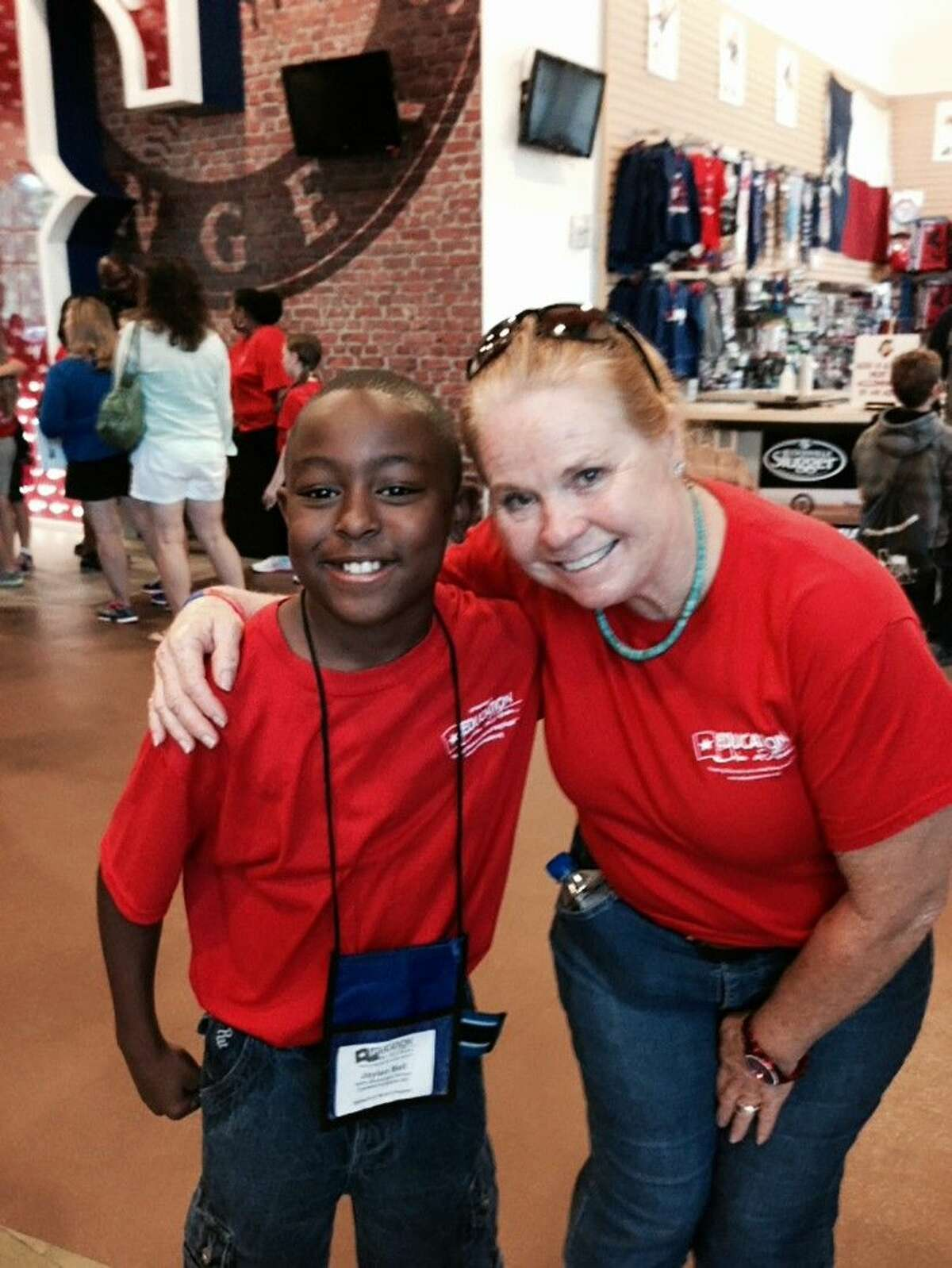 Keith Elementary School fourth-grade student Jaylen Bell stops for a picture with a Lone Star Leadership Academy representative during a Dallas/Fort Worth camp stop to Globe Life Park in Arlington - home to the Texas Rangers baseball team - on June 19.