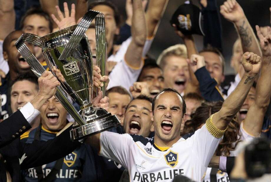 In this Nov. 20, 2011 file photo, Los Angeles Galaxy forward Landon Donovan holds up the MLS Cup after they won their championship soccer match against the Houston Dynamo in Carson, Calif.