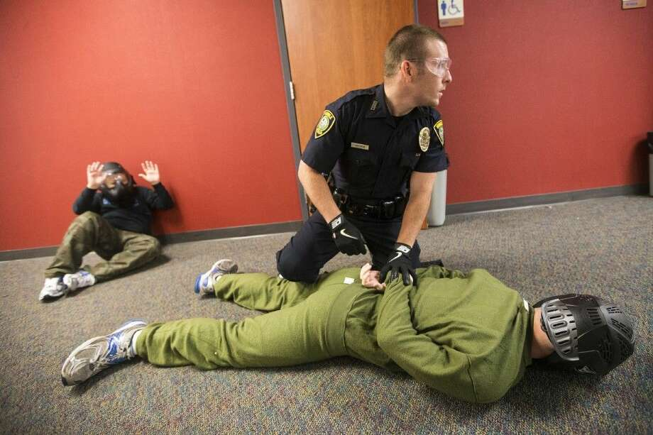 "At a 2014 police training class, Humble Police officer Kole Holden secures a ""shooter"" at Atascocita High School. Photo: Andrew Buckley"