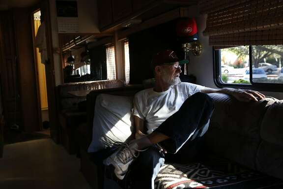 Scotty Whaley looks out the window of his RV, where he currently lives on Crisanto Ave. where nearly 40 RVs and vehicles are parked next to Rengstorff Park Oct. 4, 2016 in Mountain View, Calif. Whaley, who used to live in a van, spent his savings to buy the RV so that he could afford a place to live.