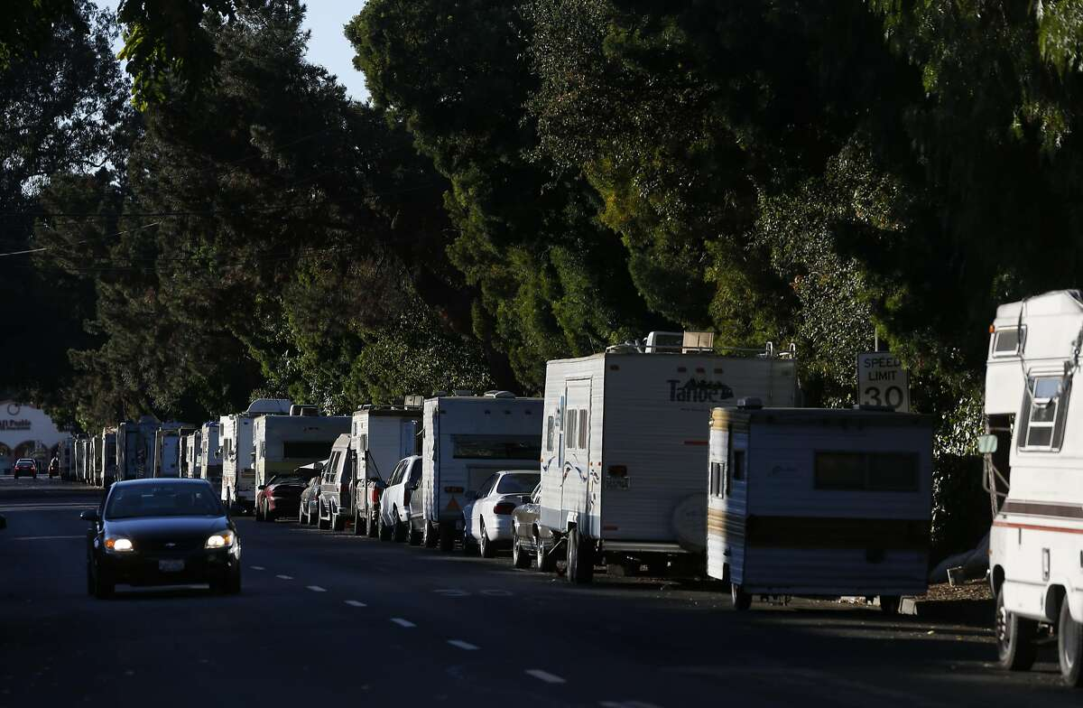 A car drives down Crisanto Ave. where nearly 40 RVs and vehicles are parked next to Rengstorff Park Oct. 4, 2016 in Mountain View, Calif.