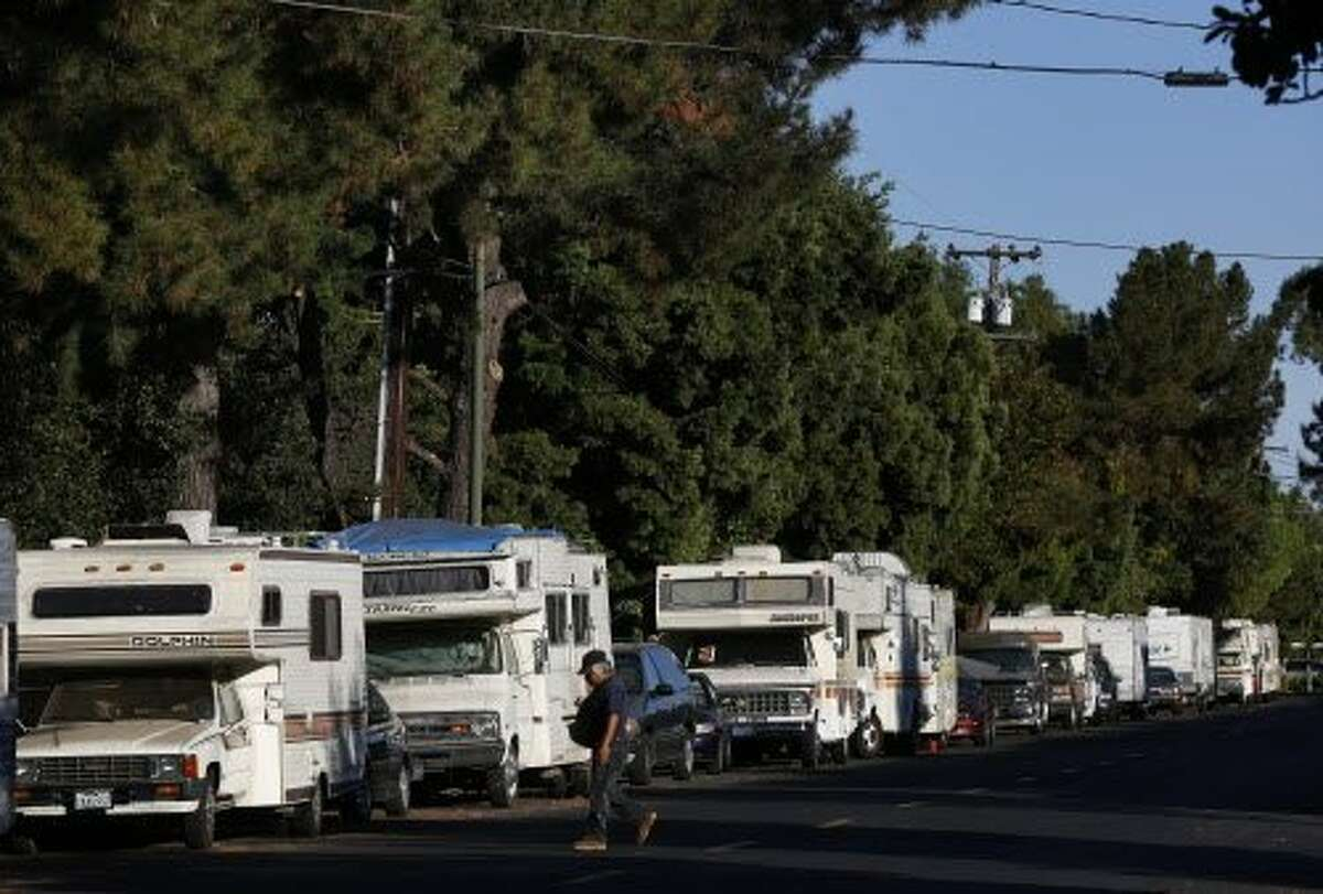 A man crosses Crisanto Ave. where nearly 40 RVs and vehicles are parked next to Rengstorff Park Oct. 4, 2016 in Mountain View, Calif.