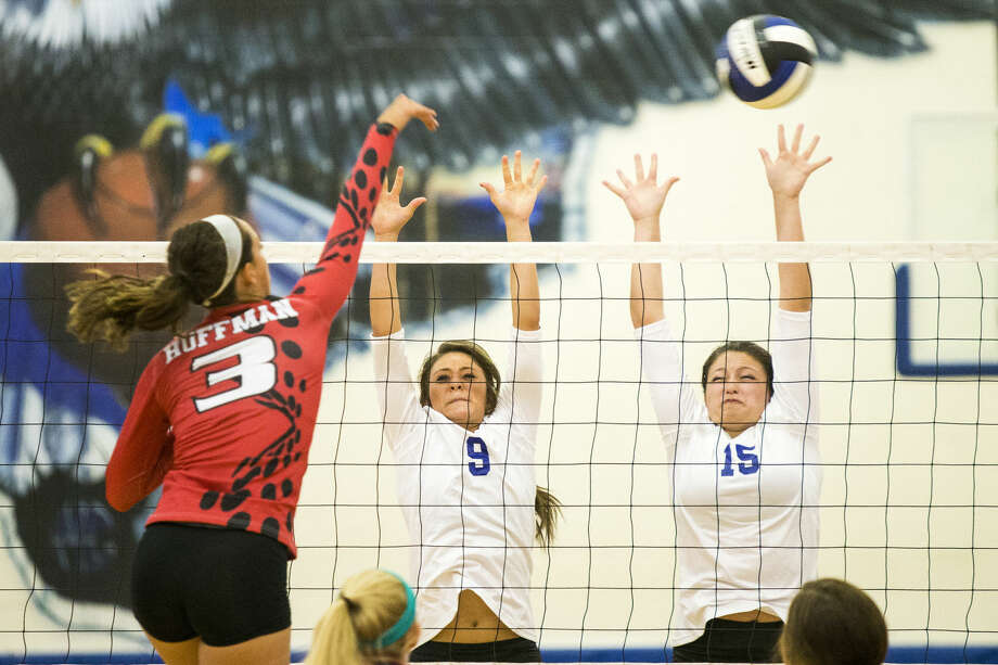 New Caney's Heather Davis (9) and Lissann Cox (15) attempt a block during Huffman's victory over New Caney on Aug. 12, 2014, at New Caney High School.