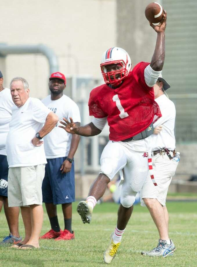 Lamar quarterback J.W. Ketchum, under the watchful eyes of Texans head coach Tom Nolen, left, and his staff, fires a pass on the run during the team's intrasquad scrimmage/cookout Saturday morning at the high school. Lamar will hold its first scrimmage this Saturday morning when they travel north to Spring to face the Dekaney Wildcats. Photo: Kevin B Long