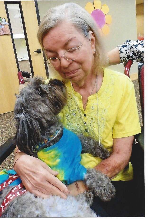 "Dressed in a Flower Power Tie-Dye shirt, pet ""Chewie Chabaca"" is being loved by guest, Annette."
