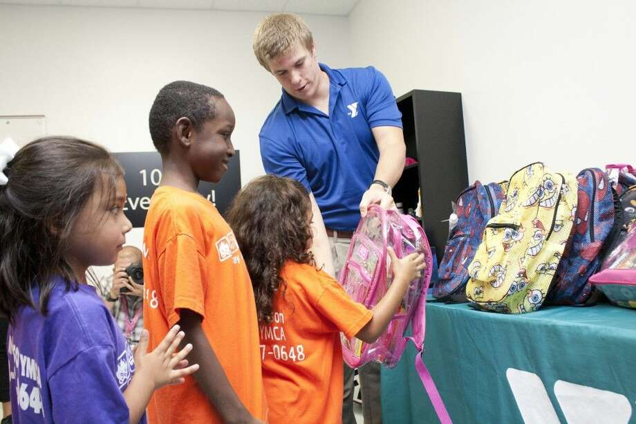 A YMCA volunteer hands delighted children their backpacks full of school supplies. Operation Backpack's 2015 campaign kicked off on Wednesday, July 15 and runs through August 9. Photo: Submitted
