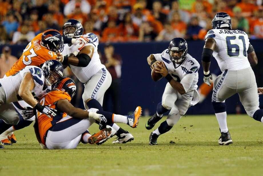 Seattle Seahawks quarterback Russell Wilson scrambles against the Denver Broncos Thursday in Denver.