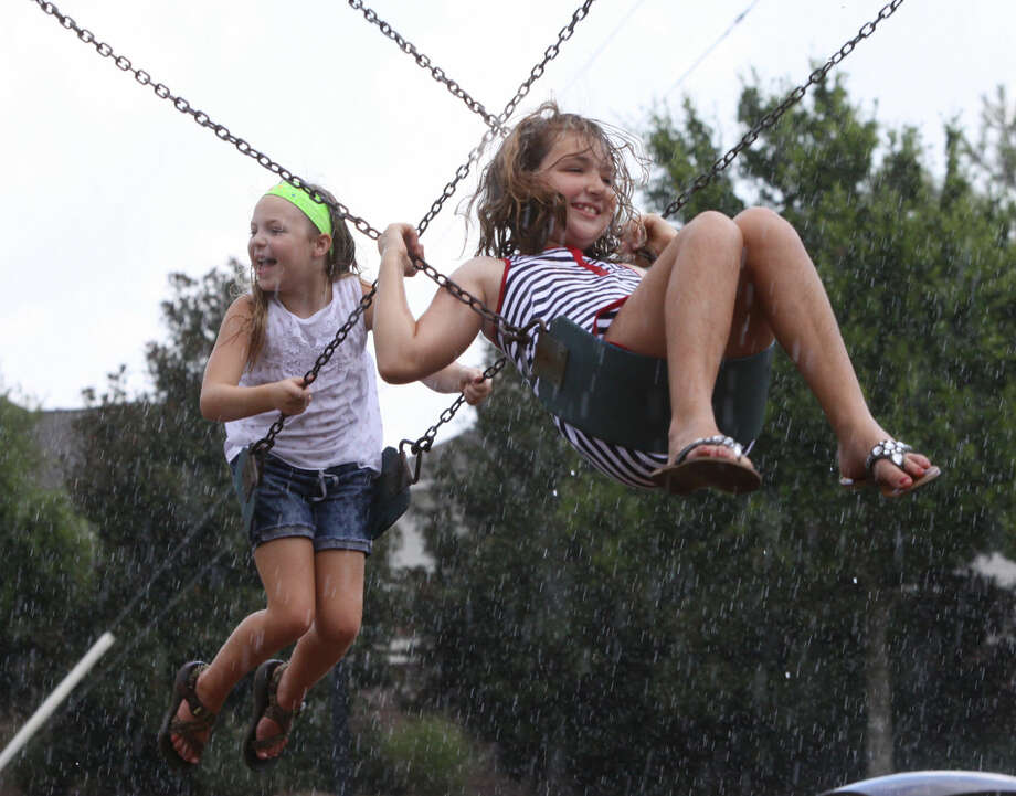 Reagan Farrow 10 (front) and Annette Walter 10 (back) swing in the rain at Seven Meadows Clubhouse in Katy, Texas on Friday, August 8, 2014. Photo: Alan Warren