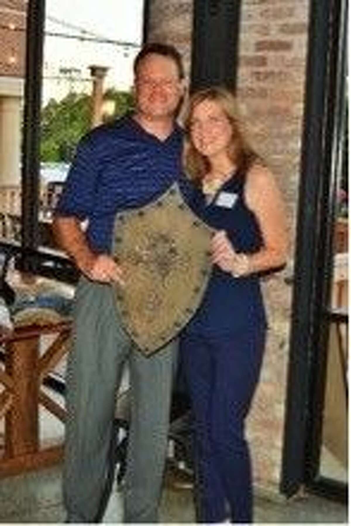 """Shield Bearer Associate Director Melissa Rotholz and husband Todd Rotholz, with the Shield Bearer """"Traveling Shield"""". The shield """"travels"""" from business to business each year as a symbol of the commitment to fighting for hearts in the community."""