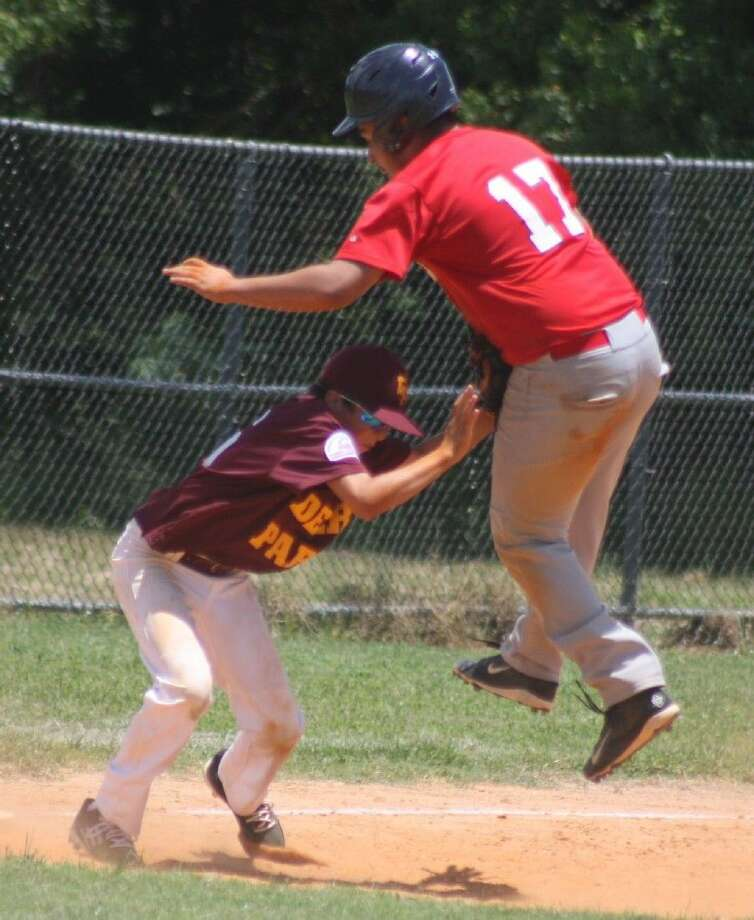 Deer Park third baseman Johnathan Vela applies the tag on a leaping Pasadena's Johnavic Deleon during their Saturday game, won easily by Deer Park. Photo: Robert Avery